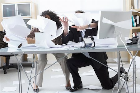 Business People Trying to Hold onto Paperwork Blowing Around on Desk Stock Photo - Premium Royalty-Free, Code: 600-02081781