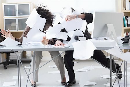 Business People Trying to Hold onto Paperwork Blowing Around on Desk Stock Photo - Premium Royalty-Free, Code: 600-02081782