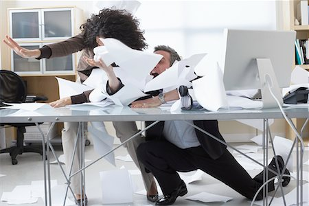 Business People Trying to Hold onto Paperwork Blowing Around on Desk Stock Photo - Premium Royalty-Free, Code: 600-02081783