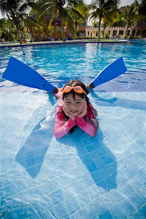 Girl Lying in Swimming Pool Wearing Goggles and Flippers Stock Photo - Premium Royalty-Free, Code: 600-02121224