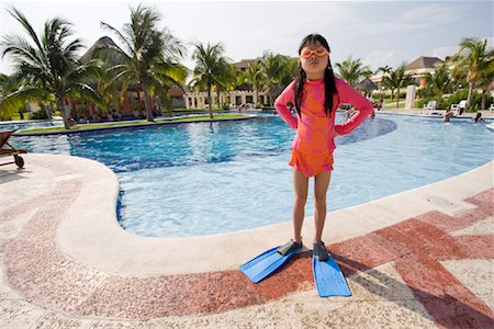 Girl Standing with Hands on Hips Next to Swimming Pool Stock Photo - Premium Royalty-Free, Code: 600-02121226