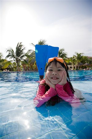 Portrait of Girl Lying in Swimming Pool Wearing Goggles and Flippers Stock Photo - Premium Royalty-Free, Code: 600-02121223