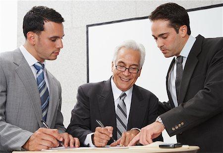 Businessmen Working Around Table Stock Photo - Premium Royalty-Free, Code: 600-02199802