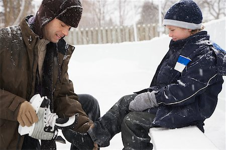 Father Helping Son Put on Skates Stock Photo - Premium Royalty-Free, Code: 600-02200079