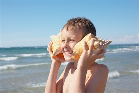 Boy Holding Seashells to His Ears, Elmvale, Ontario, Canada Stock Photo - Premium Royalty-Free, Code: 600-02265287