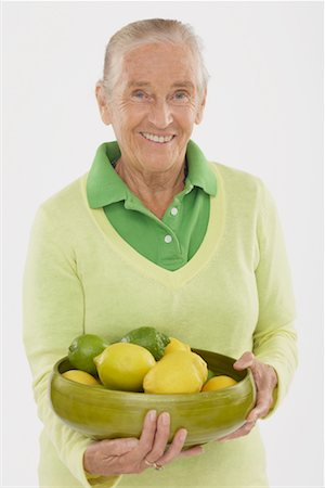 Portrait of Woman Holding Bowl of Lemons and Limes Stock Photo - Premium Royalty-Free, Code: 600-02265507