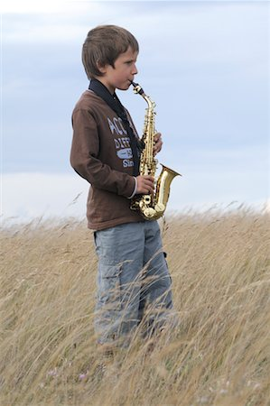 Boy Playing Saxophone in Field Stock Photo - Premium Royalty-Free, Code: 600-02290118