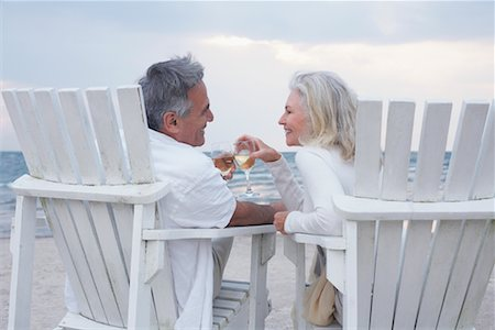 Couple Toasting with Wine while Sitting on Chairs on Beach Stock Photo - Premium Royalty-Free, Code: 600-02346334