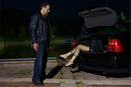 Man Looking at Dead Body in Trunk of Car Stock Photo - Premium Royalty-Free, Code: 600-02348072