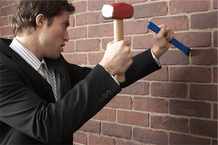 Businessman using Mallet and Chisel on Brick Wall Stock Photo - Premium Royalty-Free, Code: 600-02370941