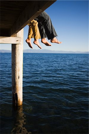 Women Dangling Feet from Dock over Lake Stock Photo - Premium Royalty-Free, Code: 600-02386146