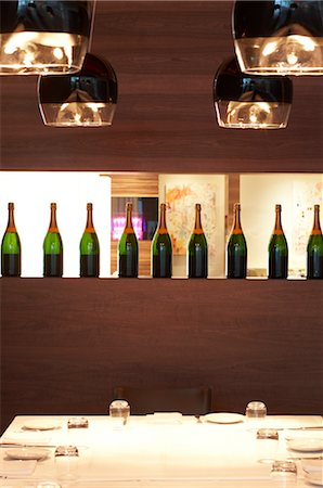 setting kitchen table - Row of Wine Bottles and Table Setting in Restaurant Stock Photo - Premium Royalty-Free, Code: 600-02429174