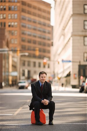 Businessman Sitting on Gas Can in the Middle of a City street Stock Photo - Premium Royalty-Free, Code: 600-02447817