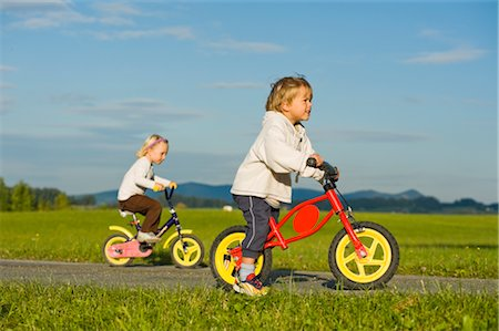 Boy and Girl Riding Bicycles,  Hof bei Salzburg, Salzburger Land, Austria Stock Photo - Premium Royalty-Free, Code: 600-02637524