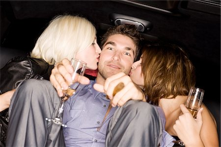 sexually aroused woman - Women Kissing Man in Back of Limousine Stock Photo - Premium Royalty-Free, Code: 600-02637979