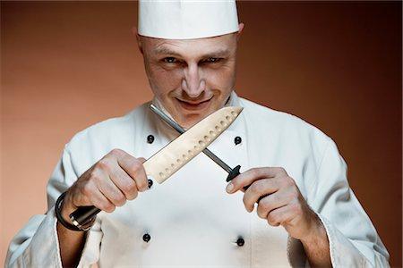Portrait of Chef Sharpening Knife Stock Photo - Premium Royalty-Free, Code: 600-02659656