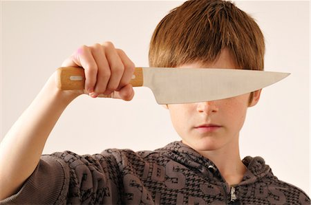 Boy Holding Knife in Front of Eyes Stock Photo - Premium Royalty-Free, Code: 600-02670199