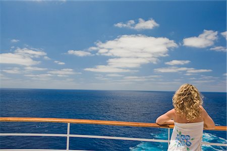 Woman Looking at Ocean from Stern of Cruise Ship Stock Photo - Premium Royalty-Free, Code: 600-02671108