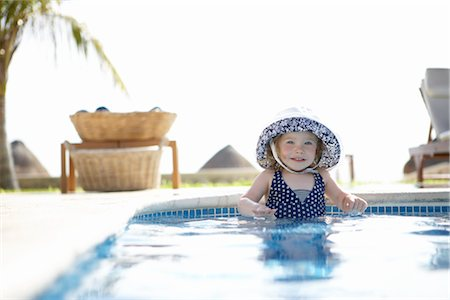 Girl Wearing Sunhat Standing in Swimming Pool, Cancun, Mexico Stock Photo - Premium Royalty-Free, Code: 600-02686152