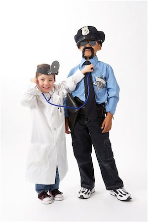 female police officer happy - Girl Dressed as Doctor Checking Boy Dressed as Police Officer Stock Photo - Premium Royalty-Free, Code: 600-02693712
