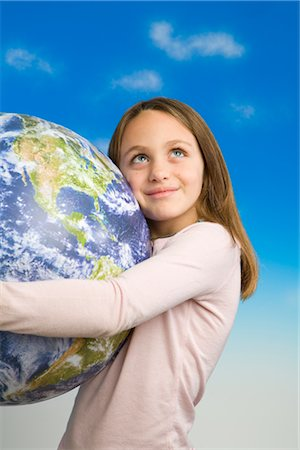 Little Girl Holding a Model of Earth as Seen From Outer Space Stock Photo - Premium Royalty-Free, Code: 600-02757052