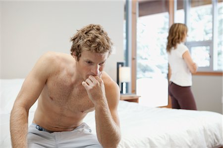 sad lovers break up - Man Sitting on Edge of Bed and Woman looking out Window in Background Stock Photo - Premium Royalty-Free, Code: 600-02757308
