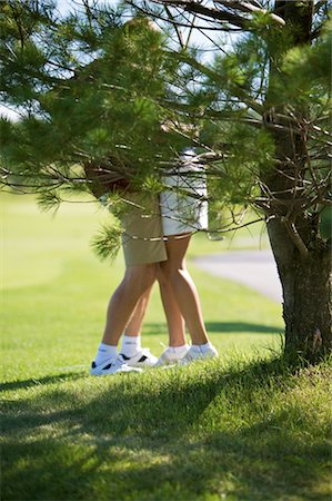 sexy women legs - Couple Embracing behind Tree on Golf Course Stock Photo - Premium Royalty-Free, Code: 600-02751477