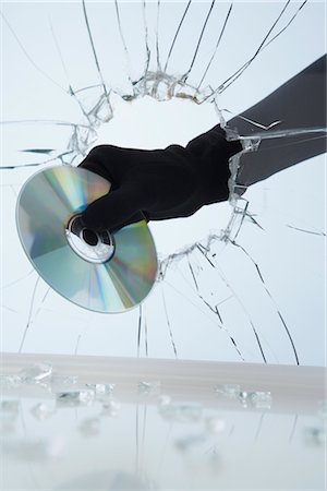 Hand Stealing CD Through Broken Glass Stock Photo - Premium Royalty-Free, Code: 600-02801120