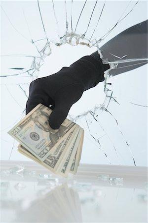 Gloved Hand Stealing Money Through Broken Window Stock Photo - Premium Royalty-Free, Code: 600-02801122