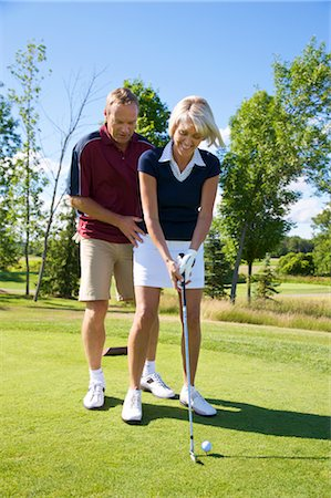 Man Helping Woman With Her Golf Swing Stock Photo - Premium Royalty-Free, Code: 600-02833099