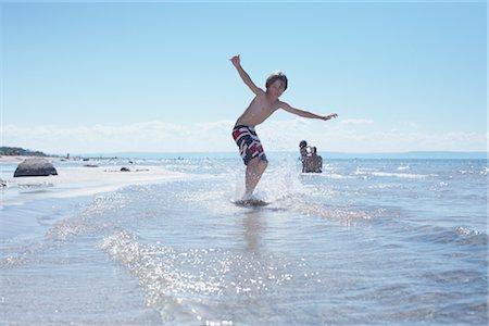 Boy Skimboarding at Deanlea Beach, Elmvale, Ontario, Canada Stock Photo - Premium Royalty-Free, Code: 600-02887089