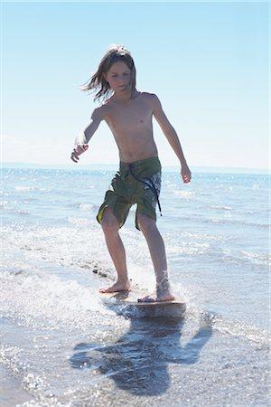 Boy Skimboarding at Deanlea Beach, Elmvale, Ontario, Canada Stock Photo - Premium Royalty-Free, Code: 600-02887095