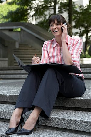 Woman Talking on Cell Phone Outdoors Stock Photo - Premium Royalty-Free, Code: 600-02887653