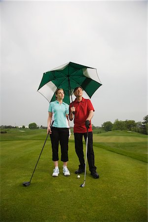 Father and Daughter on the Golf Course Holding a Large Umbrella Stock Photo - Premium Royalty-Free, Code: 600-02883090