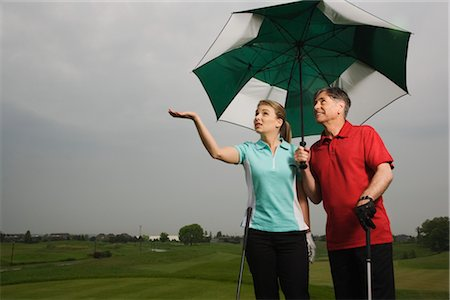 Father and Daughter on the Golf Course Holding a Large Umbrella Stock Photo - Premium Royalty-Free, Code: 600-02883091