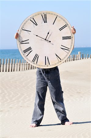 sand clock - Boy Holding a Large Clock on the Beach Stock Photo - Premium Royalty-Free, Code: 600-02912548