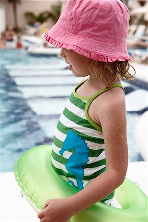 Little Girl With Inner Tube Playing on Pool Deck Stock Photo - Premium Royalty-Free, Code: 600-02967521