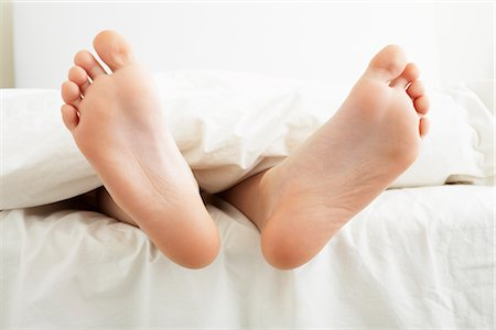 Close-up of Boy's Feet Hanging Off the End of the Bed Stock Photo - Premium Royalty-Free, Code: 600-03017678