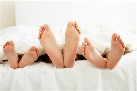 Close-up of Family's Feet in Bed Stock Photo - Premium Royalty-Free, Code: 600-03017679