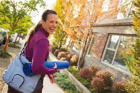 Woman Walking and Carrying Yoga Mat, Seattle, Washington, USA Stock Photo - Premium Royalty-Free, Code: 600-03017951