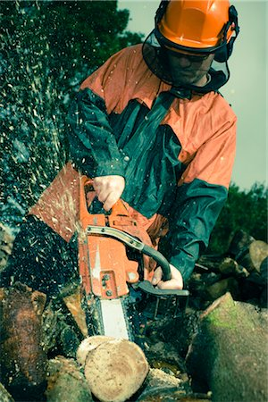 forestry - Man Cutting Tree with Chainsaw Stock Photo - Premium Royalty-Free, Code: 600-03053768
