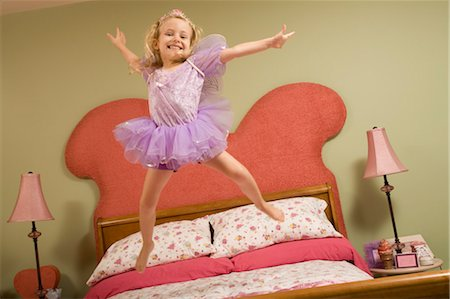Little Girl Dressed as Fairy Jumping on Bed Stock Photo - Premium Royalty-Free, Code: 600-03152488