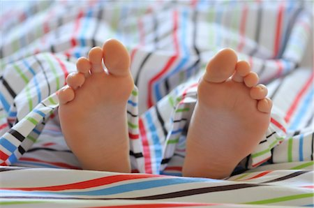 Close-up of Child's Feet in Bed Stock Photo - Premium Royalty-Free, Code: 600-03178804