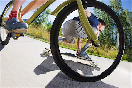 Woman Riding a Bicycle and Man Riding a Skateboard on a Bike Path, Steamboat Springs, Routt County, Colorado, USA Stock Photo - Premium Royalty-Free, Code: 600-03210490