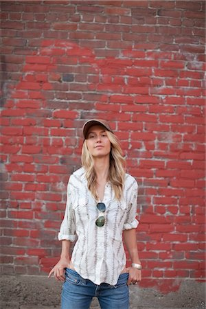 Portrait of Woman Standing in Front of Brick Wall Stock Photo - Premium Royalty-Free, Code: 600-03392374