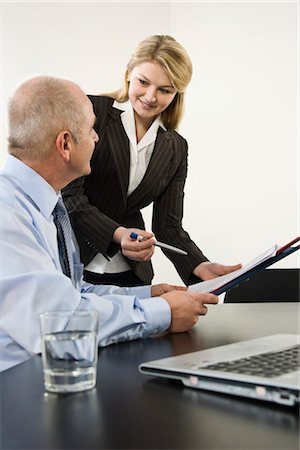 Businesswoman Giving Paper to Businessman to Sign Stock Photo - Premium Royalty-Free, Code: 600-03404525