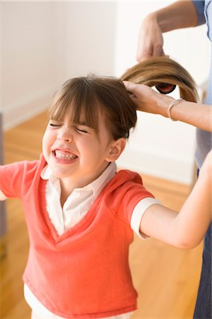 Girl Unhappy with having Hair Brushed Stock Photo - Premium Royalty-Free, Code: 600-03403632