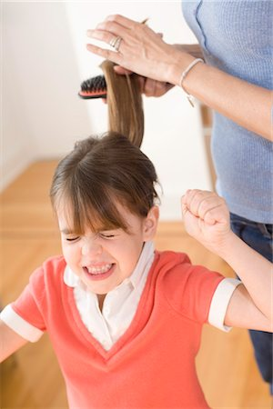Girl Unhappy with having Hair Brushed Stock Photo - Premium Royalty-Free, Code: 600-03403633