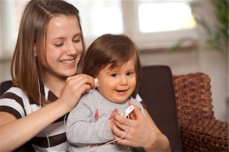Teenage Girl with Baby Boy Listening to MP3 Player, Mannheim, Baden-Wurttemberg, Germany Stock Photo - Premium Royalty-Free, Code: 600-03456197