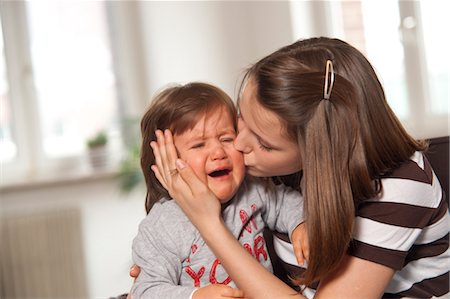 Teenage Girl Kissing Crying Baby Boy, Mannheim, Baden-Wurttemberg, Germany Stock Photo - Premium Royalty-Free, Code: 600-03456199